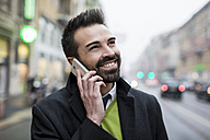 Smiling businessman in the city on cell phone - MAUF01106