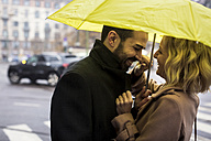Happy business couple under umbrella in the city - MAUF01109