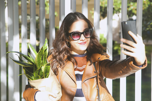 Young woman carrying potted plant taking selfie with smartphone - RTBF00934