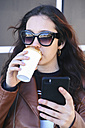 Portrait of young woman with coffee to go taking selfie with smartphone - RTBF00949