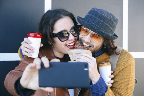 Young couple with croissant and coffee to go taking selfie with smartphone - RTBF00952