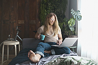 Bearded young man with long hair using laptop and drinking coffee at home - RTBF00955