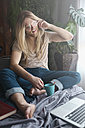 Man with long hair and beard using smartphone on sofa bed - RTBF00958