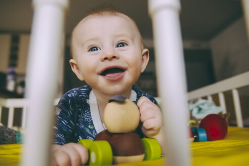 Portrait of happy baby boy with wooden toy in his crib - MFF03675