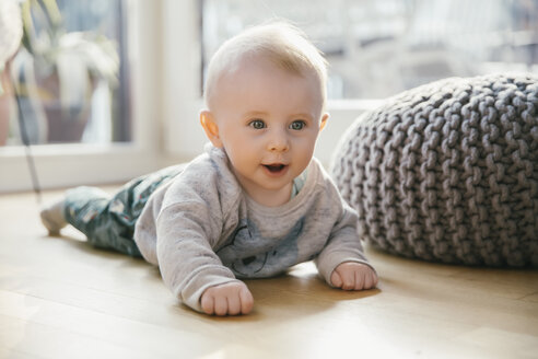 Portrait of baby boy lying on the floor - MFF03684