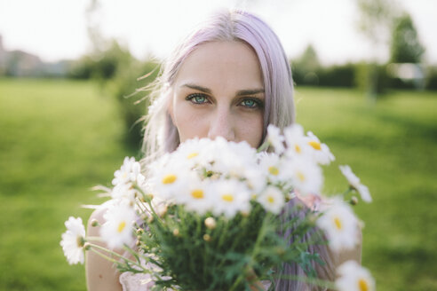Portrait of woman hiding behind bunch of daisies - GIOF02822