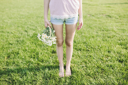Woman standing on a meadow holding bunch of daisies, partial view - GIOF02831