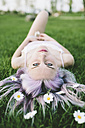 Portrait of woman lying on grass with flowers on hair - GIOF02837