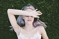 Woman lying on grass covering eyes with her arm - GIOF02840