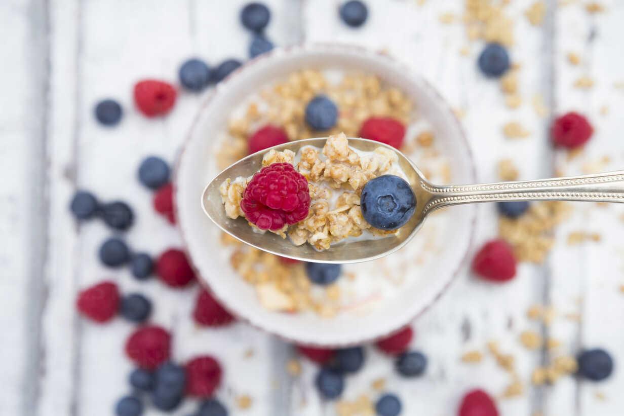 Spoon of granola with raspberry and blueberry, close-up - LVF06204 - Larissa Veronesi/Westend61