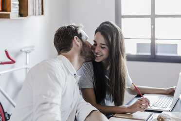 Happy couple with laptop at home kissing - GIOF02848