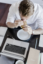 Man with laptop eating at home - GIOF02854