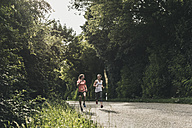 Two women running on country road - UUF10920