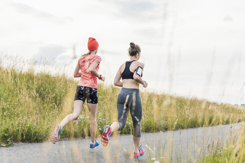 Two women running in the countryside - UUF10923