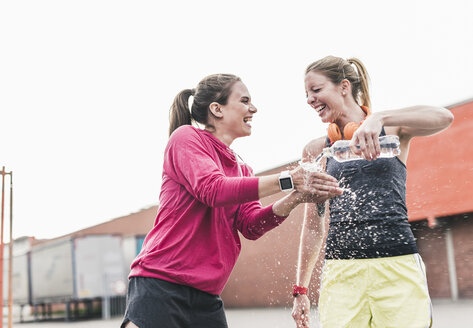 Two playful women with water bottle having a break from exercising - UUF10932