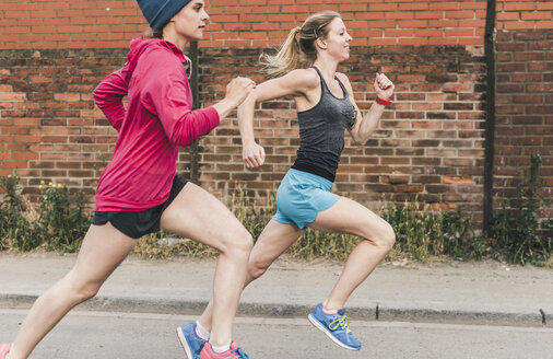 Two women running on the street - UUF10935