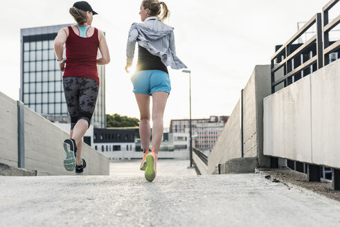 Two women running in the city - UUF10938