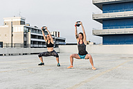 Two women exercising with kettlebells on parking level in the city - UUF10950