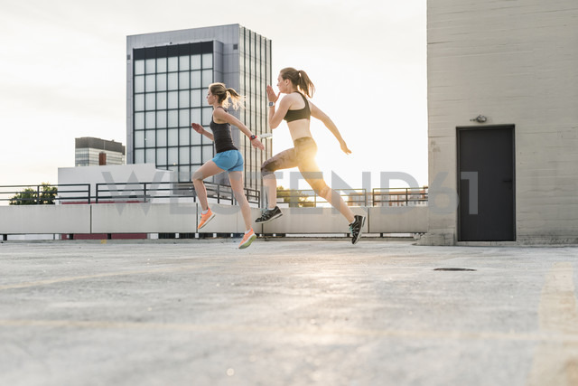 Two women exercising on parking level in the city - UUF10953