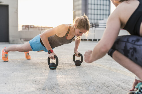 Woman cheering at training partner kettlebell on parking level in the city - UUF10956