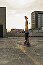 Woman doing a headstand on parking level in the city - UUF10959