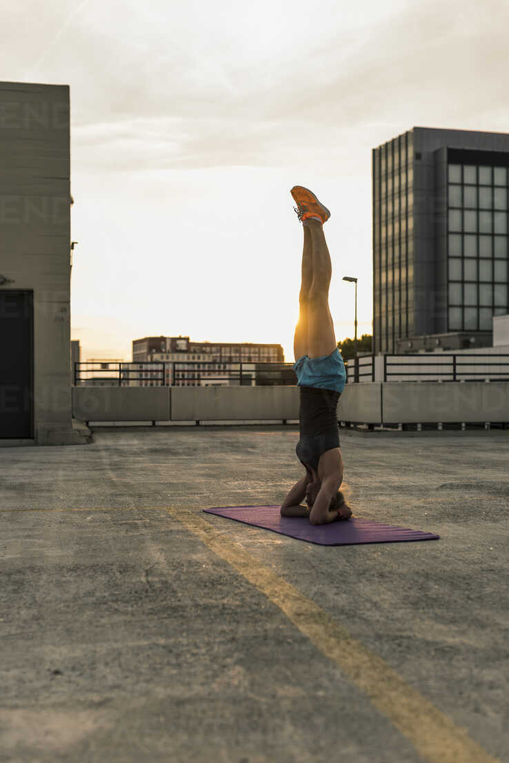 Woman doing a headstand on parking level in the city - UUF10959 - Uwe Umstätter/Westend61