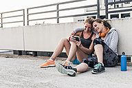 Two women having a break from exercising sharing smartphone - UUF10968