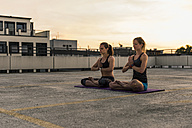Two women practicing yoga on parking level in the city - UUF10974