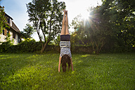 Back view of girl doing handstand on a meadow - LVF06205