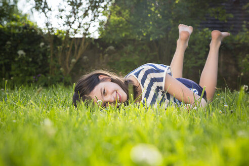 Portrait of smiling girl lying on a meadow in summer - LVF06208