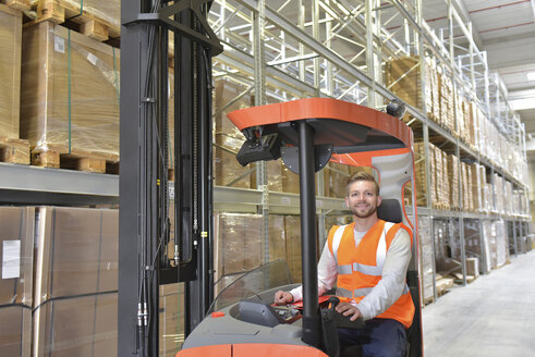 Portrait of smiling man in factory hall on forklift - LYF00732
