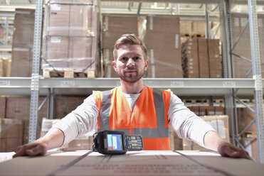 Portrait of confident man in factory hall with barcode scanner - LYF00735