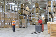 Man in factory hall and moving forklift - LYF00741