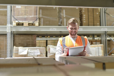 Smiling man in factory hall wearing safety vest holding clipboard - LYF00756