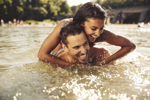 Laughing couple bathing together in river - SUF00153