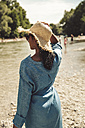 Woman wearing straw hat and jeans dress on the beach - SUF00159