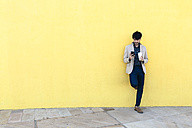 Young man with coffee to go checking the cell phone in front of yellow wall - GIOF02876
