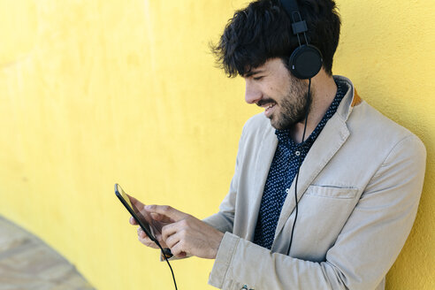 Smiling young man with headphones and cell phone - GIOF02879