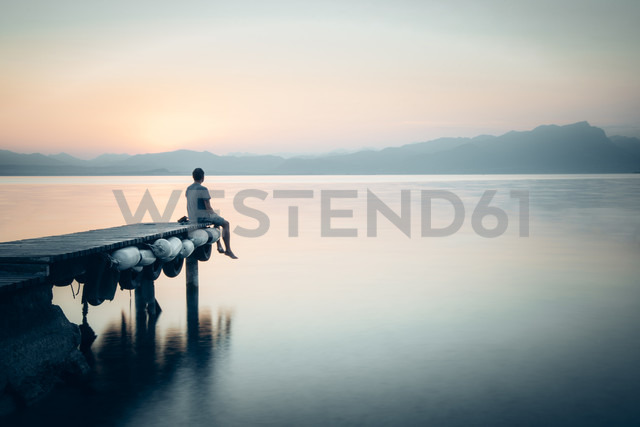 Italy, Lazise, man sitting on jetty looking at Lake Garda - IPF00393 - Ina Peters/Westend61