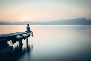 Italy, Lazise, man sitting on jetty looking at Lake Garda - IPF00393