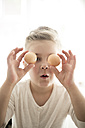 Portrait of little girl with two brown eggs - MOEF00028