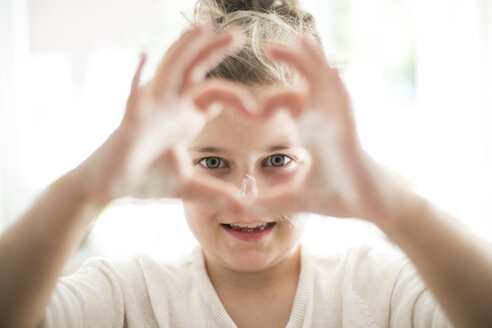 Portrait of little girl shaping heart with her fingers - MOEF00046