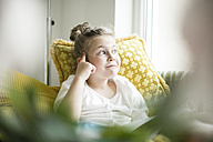 Portrait of thinking little girl sitting with magazine on armchair - MOEF00049
