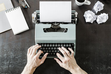 Close-up of man using typewriter with crumpled paper on desk - GIOF02892