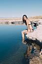 Chile, Atacama Desert, portrait of woman sitting on edge of Laguna Cejar - GEMF01719