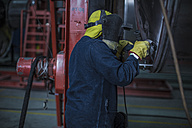 Worker wearing welding mask in factory - ZEF14052