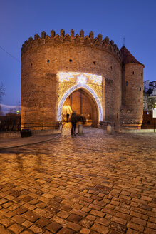 Poland, Warsaw, Old Town, cobbled street and Barbican fortification at night - ABOF00199