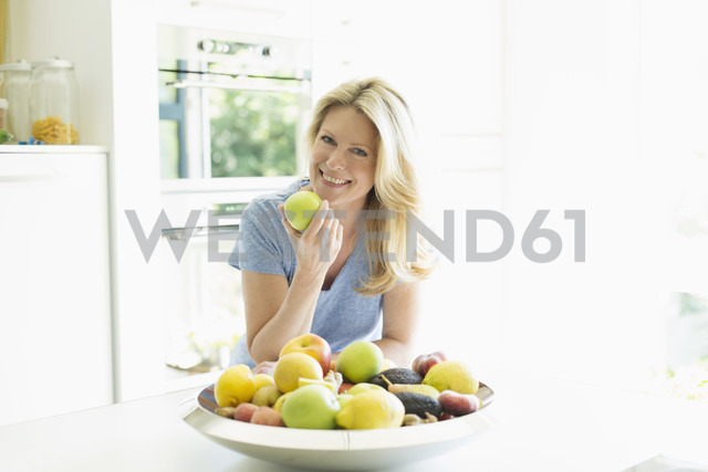 Portrait of smiling woman at home eating an apple - MAEF12241 - Roman Märzinger/Westend61