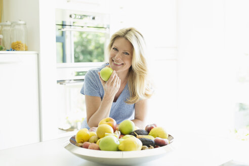 Portrait of smiling woman at home eating an apple - MAEF12241