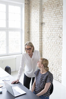 Mature businesswoman working with younger colleague in office - RBF05752
